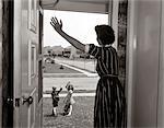 1950s MOM IN DOORWAY WAVING AT BOY & GIRL GOING TO SCHOOL