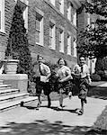 1940ER JAHRE GRUPPE VON DREI SCHULKINDER 2 BOYS 1 GIRL LIEF BÜRGERSTEIG TRAGEN BÜCHER