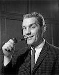 1950s PORTRAIT OF MAN IN TWEED JACKET SMOKING PIPE SMILING INDOOR