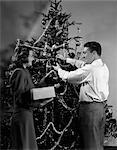 1940s COUPLE DECORATING CHRISTMAS TREE WITH CHRISTMAS BALLS