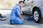 Mechanic changing car's flat tire