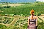 Vue arrière du femme regardant le vignoble dans le Chianti, Toscane, Italie