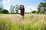 Homme, jouer au golf dans les hautes herbes