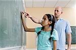 A girl writing on a blackboard with a teacher standing beside