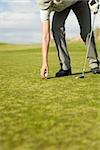A woman putting a golf ball on a tee