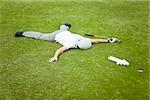A golfer lying on a putting green behind an arrow of golf balls