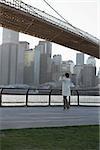 Une femme prenant une photographie près de la ville de Brooklyn Bridge, New York