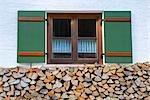 Brennholz gestapelt vor Fenster von Bauernhaus, Berchtesgaden, Bayern, Deutschland