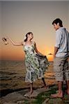 Jeune couple debout sur les rochers surplombant l'océan