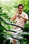 Un homme utilise son téléphone portable, tel qu'il est dans les escaliers, environnée par les arbres
