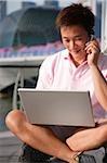 Homme travaillant sur ordinateur portable tout en parlant sur l'extérieur du téléphone