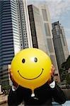 Homme tenant un ballon de smiley face