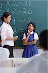 teacher and girl at chalkboard