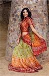 jeune femme en sari marche, pilier en pierre