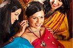 trois femmes en saris, un placement bijoux sur un autre