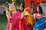 trois femmes en saris, jetant des pétales