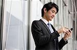 Homme d'affaires envoyant le message sur l'appareil mobile
