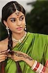 woman wearing sari and decorated with henna tattoo, traditional jewelry and bindi