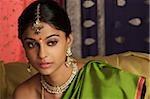 woman wearing sari, surrounded by sari fabric, decorated with henna tattoos, jewelry and bindi