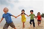 Four kids running down the beach holding hands.