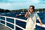 S'appuyant sur la rambarde parlant au téléphone cellulaire, l'eau dans le fond de l'homme
