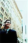 Exécutif homme lunettes de soleil à l'aide de téléphones cellulaires, bâtiment à l'arrière-plan (élevés des céréales)