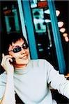 Jeune homme, robe causale, lunettes de soleil à l'aide de téléphones cellulaires (élevés des céréales)
