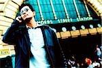 L'homme à l'aide de téléphones cellulaires, de la gare en arrière-plan