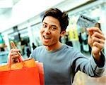 Jeune homme tenant des sacs à provisions et carte de crédit, souriant.