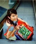 Woman holding shopping bags sitting on escalator.