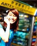 Jeune femme à l'aide de téléphones cellulaires, boutiques à l'arrière-plan.