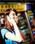 Jeune femme à l'aide de téléphones cellulaires, en riant, boutiques à l'arrière-plan.