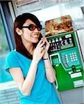 Jeune femme avec des lunettes de soleil sur le téléphone public.