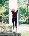 Jeune femme debout avec les bras tendus, fontaine en arrière-plan.