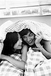 Man and woman under sheet, talking