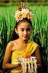 Danseur de jeunes balinais de Bali, en Indonésie, en costume avec des offrandes de riz paddy.