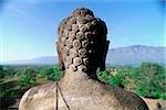 Figure de Bouddha de Java, en Indonésie, au temple de Borobudur, montagnes en arrière-plan