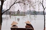 Vietnam, Hanoi, Two women sit on a bench overlooking Huan Kiem Lake.