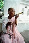 Myanmar, Mandalay area, Nun smoking cigar while holding prayer beads