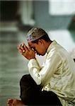 Malaysia, Kuala Lumpur, Malay man holds a small Koran and prays.