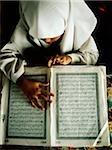Malaysia, Selangor, Malay girl reading the Koran written in Jawi, the Malay language written in Arabic script.