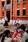 Myanmar (Burma), Yangon (Rangoon), Groups of people having tea and snacks outside a colonial brick building.