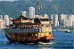 Bateau de Hong Kong, le port de Victoria, à deux étages, bâtiments en arrière-plan.