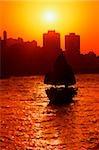 Silhouette de Hong Kong, le port de Victoria, de bateau, soleil en arrière-plan.