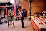 Malaysia, Kuala Lumpur, Chinatown, Man praying with joss sticks at Chinese temple.