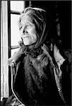 India, Ladakh, Small village near Leh, Elderly lady looking out of window.