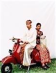 Indonésie, Bali, Ubud, couple de mariage balinais en tenue de cérémonie, assis sur le scooter de moteur, femme portant l'offre.