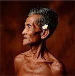 Indonesia, Bali, Ubud, Mature Balinese man with Frangipani flower adornment.