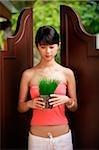 Young woman standing between door panels, holding plant