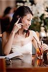 Jeune femme à l'aide du téléphone mobile dans un café